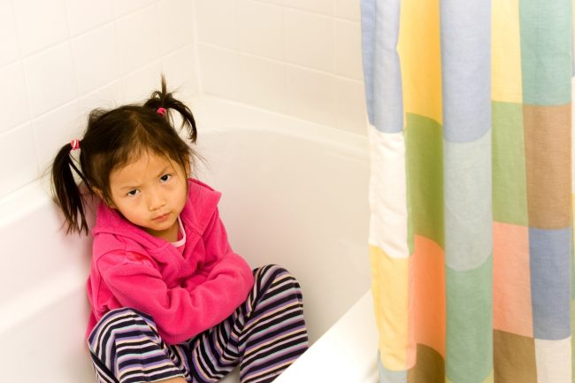 Little girl throwing a tantrum hides in the bathtub