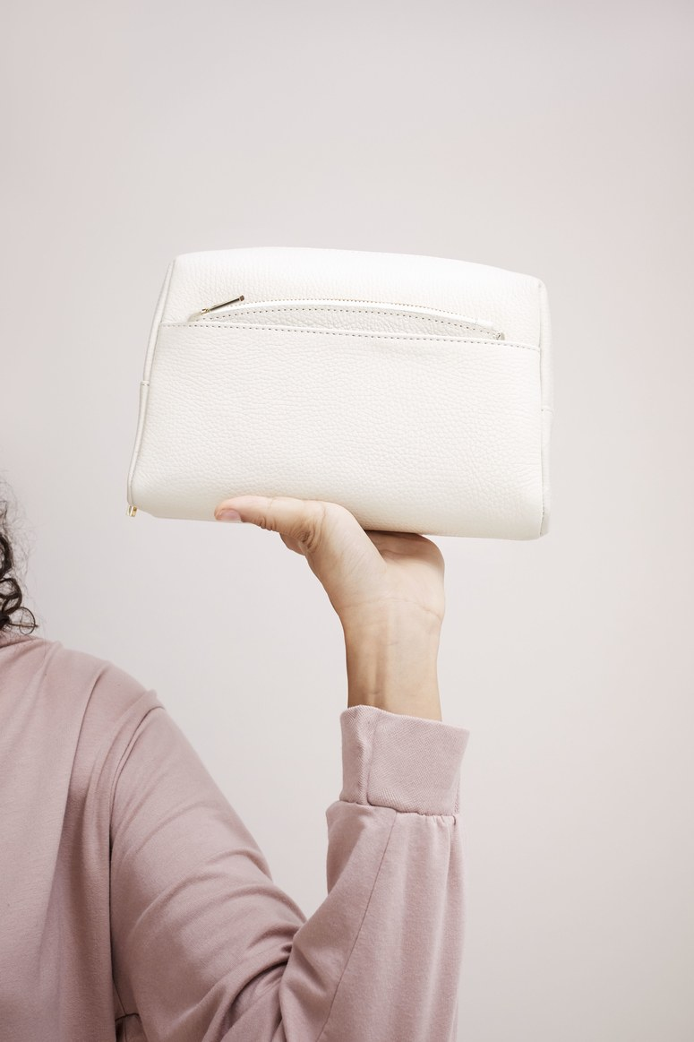 Someone holding the white version of Cuyana vanity bag designed by makeup artist Daniel Martin